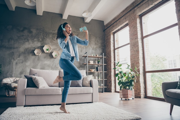 Full body photo of beautiful dark skin wavy lady holding telephone like microphone wear modern earflaps singing sitting floor near couch casual denim outfit living room indoors