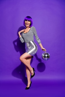 Full body photo of charming lady with eyewear eyeglasses hold mirror ball dressed in striped shirt isolated over purple violet background