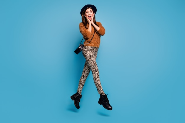 Full body photo of crazy funky girl have fun fall spring holiday see black friday bargain scream wow omg jump wear casual style clothes clutch isolated over blue color wall