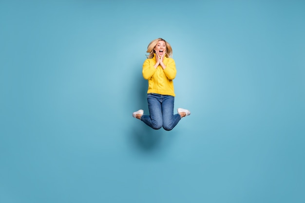 Full body photo of crazy lady jumping high celebrating free trip abroad rejoicing hands on cheekbones wear knitted yellow pullover jeans isolated blue color wall