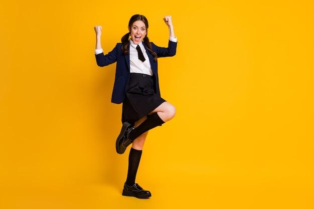 Full body photo of ecstatic high school teen girl raise fists scream yes