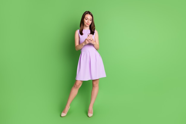 Full body photo of elegant fashionable girl lady hold look mobile discontent followers dislike unsubscribe blog fail hate comment wear violet dress isolated pastel green color background