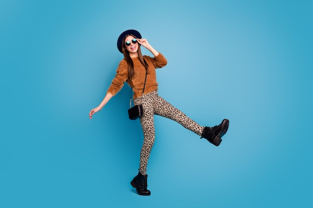 Full body photo of funky crazy girl enjoy winter holiday walk feel content wear good look outfit isolated over blue color wall