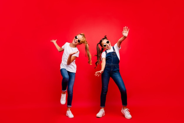 Full body photo of funky funny crazy two brown blonde hair girlfriends with tails fun weekends holidays dance scream wear white modern outfit isolated over red color background Premium Photo
