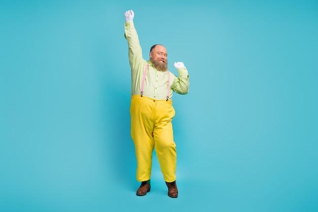 Full body photo of funky man dancing over  blue background