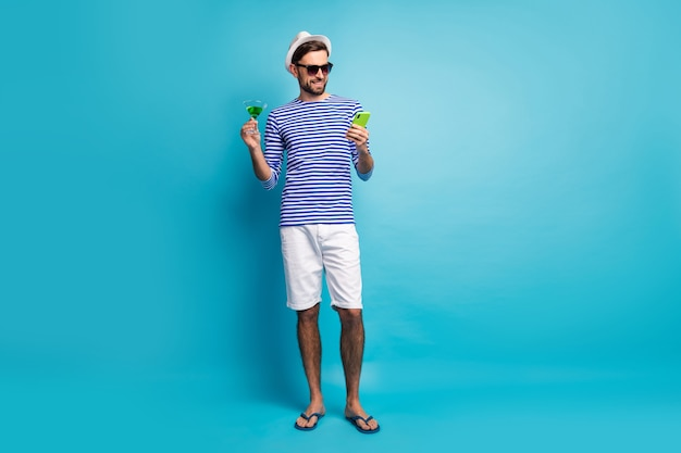 Full body photo of funky traveler guy browsing telephone drink green cocktail all inclusive resort wear sun specs striped sailor shirt cap shorts flip flops isolated blue color