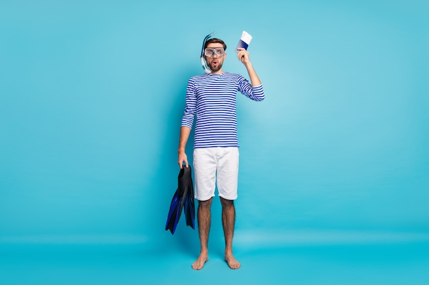 Full body photo of funny guy tourist yacht voyage showing diver license hold underwater mask breathing tube flippers wear striped sailor shirt shorts isolated blue color