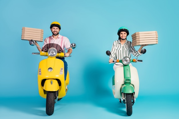 Full body photo of funny lady guy drive two vintage moped carry pizza boxes courier occupation junk fastfood formalwear outfit protective helmet isolated blue color wall