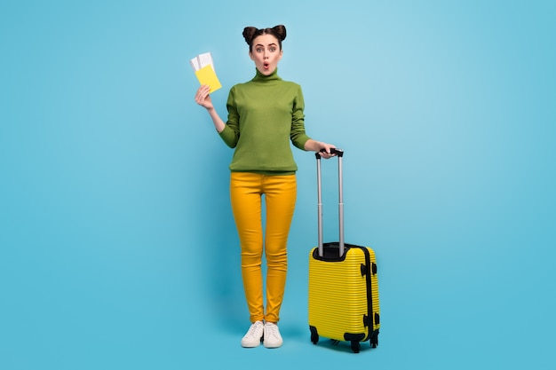 Full body photo of funny pretty lady hold tickets passport cheap flight abroad rolling suitcase wear green turtleneck yellow pants footwear isolated blue color wall