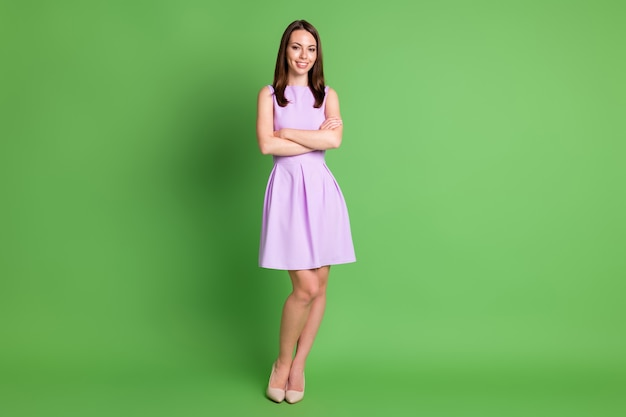 Full body photo of gorgeous smiling girl lady crossed hands slim legs flirty stand posing advert recruiting agency wear violet dress beige shoes isolated pastel green color background