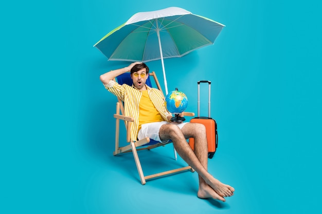 Full body photo guy rest relax shocked borders quarantine close touch hand head sit deckchair umbrella bag luggage wear yellow white striped shirt short isolated blue color background