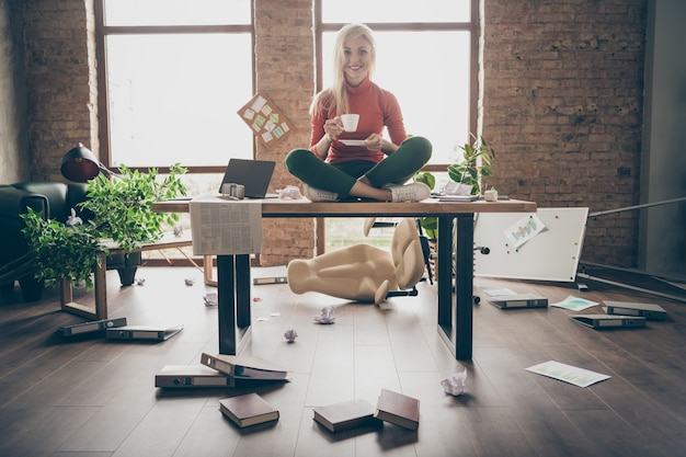 Full body photo of happy trader woman sit on table crossed legs feel carefree careless rest relax hold white coffee cup in messy office loft