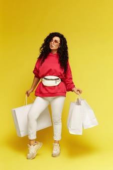 ピンクのパーカーとモダンなスニーカーで買い物袋を保持し、黄色の背景の上に孤立してポーズをとるモデルの女の子の全身写真