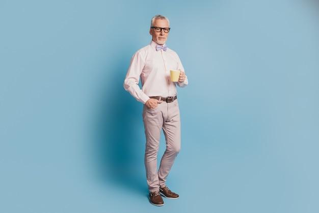 ホットコーヒーを飲む年配のハンサムなビジネスマンの全身写真