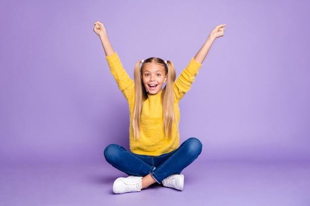 驚いた子供の座っている足を組んで折りたたまれた勝利の競争の全身写真は、紫色の壁の上に分離されたスタイリッシュな服を着て拳を叫びます