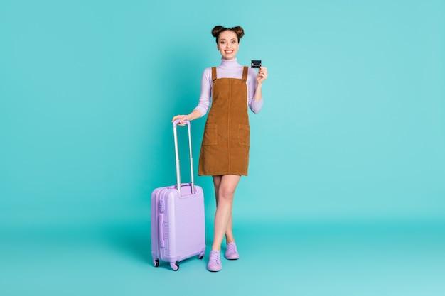 국제 여행 플라스틱 카드를 들고 있는 매력적인 쾌활한 긍정적인 2개의 빵 여성 승객의 전신 사진은 라일락 수하물을 입고 봄 옷을 입고 격리된 청록색 배경