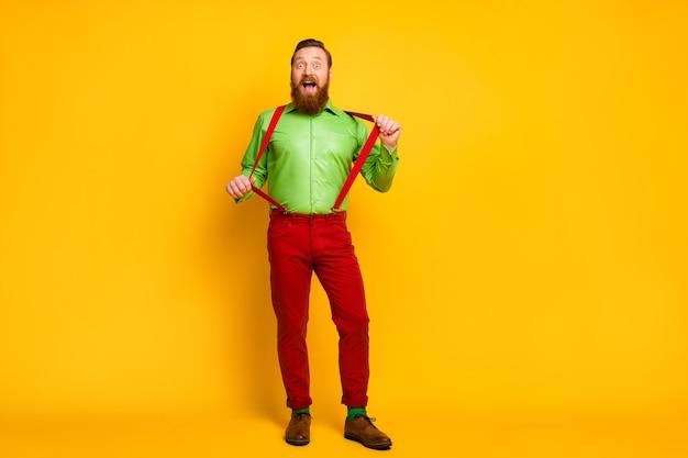 매력적인 재미 있은 남자 모델의 전신 사진 좋은 분위기 장난기 많은 사나이 착용 녹색 셔츠 빨간 멜빵 바지 양말 신발 절연 생생한 컬러