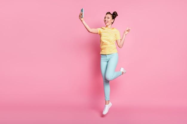 Фотография всего тела привлекательной женщины с телефоном в руке, вскакивающей и делая селфи