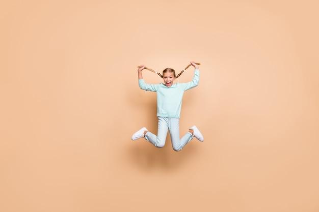 Фото всего тела красивой забавной маленькой леди, прыгающей высоко, держите длинные косы, руки, возбужденные, хорошее настроение, выходные, носите синий свитер, джинсовую обувь, изолированную бежевую цветную стену