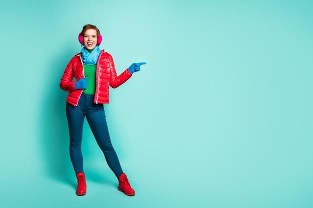 美しい女性が指を向ける全身写真空きスペースオファーセール価格最終シーズン着用赤いオーバーコート青いスカーフピンクの耳カバーパンツブーツ孤立したティールカラーの壁