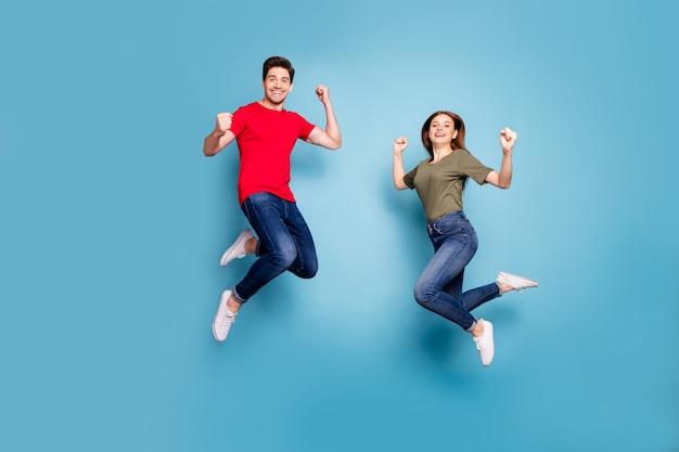 Фото всего тела коричневой рыжеволосой романтической пары в прыжке, шоу бицепсов, трицепсов, наслаждающихся мощной одеждой, современной молодежной одеждой, изолированной на синем фоне