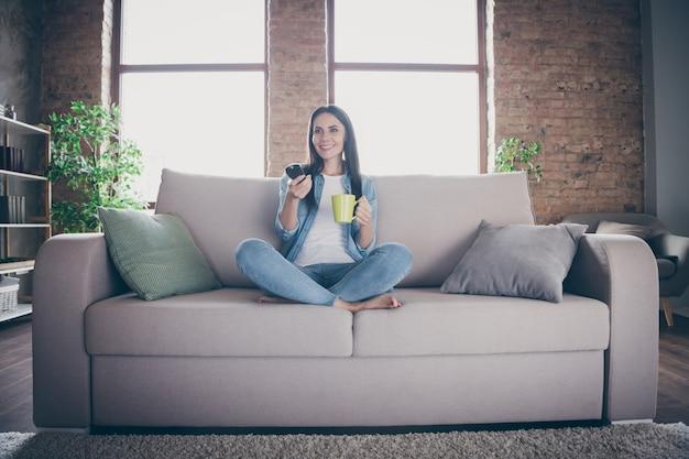 쾌활한 귀여운 소녀의 전신 사진은 covid19 격리 휴식 휴식 자유 시간 휴식 소파 다리를 건너 tv 스위치 채널을 시청 실내에서 카카오 커피 잔을 집에서 즐기십시오