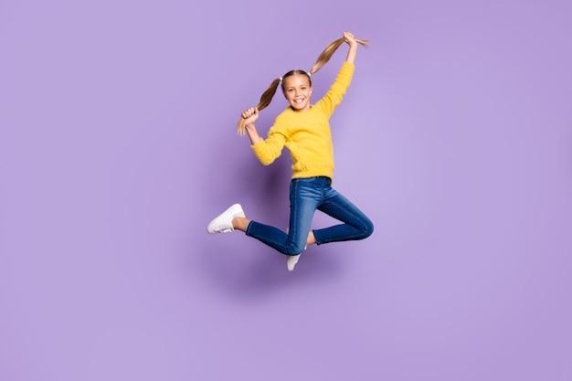 Фотография всего тела веселого симпатичного ребенка, развлекающегося на весенних каникулах, прыгать, удерживать косички, носить кроссовки в повседневной одежде, изолированные на стене фиолетового цвета