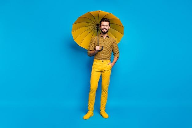 쾌활한 꿈꾸는 활기찬 남자의 전신 사진 비오는 날씨에 재미있는 자유 시간 개최 다채로운 밝은 파라솔 착용 총 노란색 모양의 운동화는 파란색 위에 절연