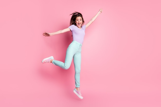 Фото всего тела веселой энергичной девушки прыгать, удерживать руку, пытаться поймать воздух, летать, ветер, дуть зонтиком, носить фиолетовую одежду, кроссовки, изолированные на пастельном цветном фоне