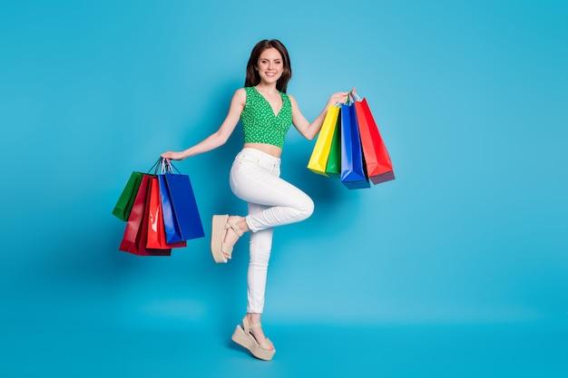 陽気な女の子のジャンプの全身写真はオフショッピングをお楽しみください-販売は多くのバッグを保持します緑の点線の一重項作物タンクを着用します-青い色の背景の上に分離された白いパンツのズボン