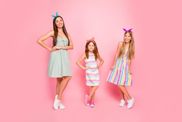 ピンクの背景の上に分離されたポーズで夏服に触れるモダンなヘッドバンドの陽気な女の子の全身写真
