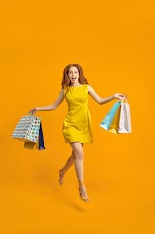 たくさんのパックを運ぶ陽気な女性ツーリストウォークショッピングセンターの全身写真、良い気分、最高の週末、ジャンプ、黄色のスタジオの背景に分離されたドレスを着て、肖像画