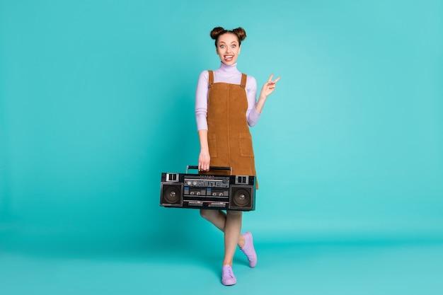 미친 쾌활한 소녀의 전신 사진은 펑키한 음악 소리를 듣는 v자 모양의 혀가 튀어나와 가을 미니 드레스 바이올렛 점퍼 운동화 격리된 청록색 배경