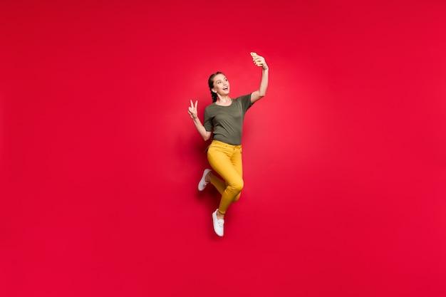 クレイジーな面白い女性が高くジャンプしてvサインのシンボルを示すセルフィーを作る全身写真陽気な気分はカジュアルな黄色のズボン緑のtシャツ孤立した赤い色の背景を着用します