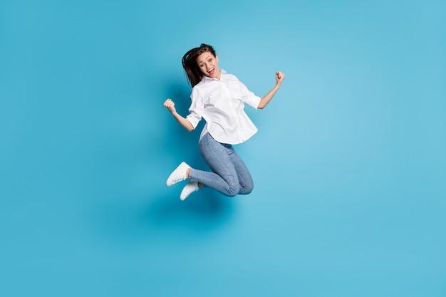 Фото всего тела сумасшедшей леди, прыгающей высоко, поднять кулаки, победа, носить белую рубашку, джинсы, туфли, изолированный синий цвет фона