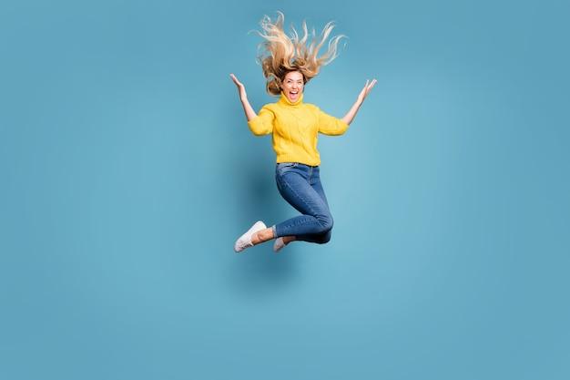 高くジャンプする狂気の女性の全身写真は、陽気な人がニットの黄色のプルオーバージーンズを着用する秋のそよ風の髪型をお楽しみください分離された青い色の壁