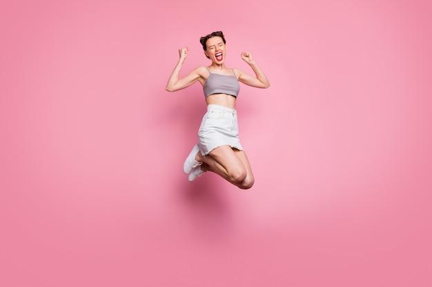 기뻐 긍정적 인 소녀의 전신 사진 점프 승리 복권 할인 뉴스 비명 예 예 주먹 올리기 기분 기뻐 감정 캐주얼 스타일 옷 절연 핑크 색상