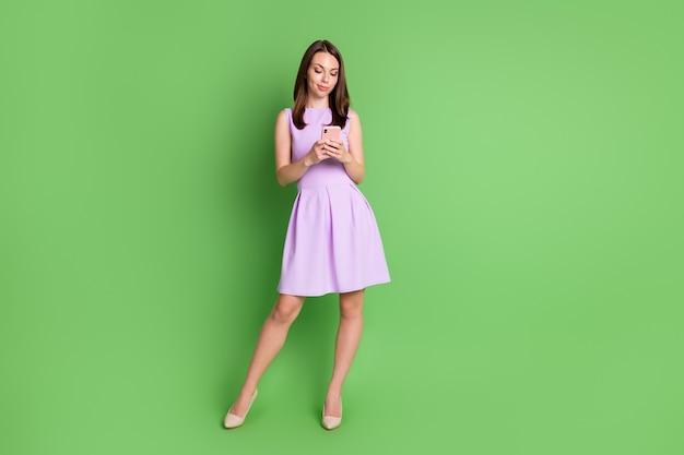 エレガントでファッショナブルな女の子の女性の全身写真ホールドルックモバイル不満フォロワー嫌い購読解除ブログ失敗嫌いコメント着用バイオレットドレス孤立パステルグリーン色背景