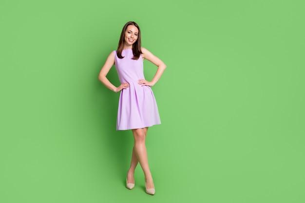 Фото всего тела очаровательной красивой молодой девушки, леди, кокетка, поза, скрещенные ноги, руки, талия, реклама, танцевальная школа, одежда, фиолетовое платье, бежевые каблуки, изолированный, пастельный зеленый цвет фона