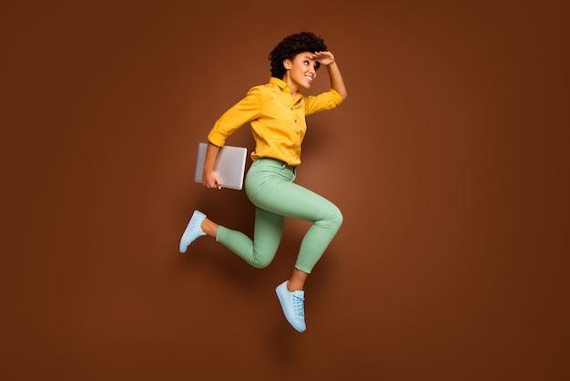 펑키 어두운 피부 레이디 점프 하이 홀드 노트북 서둘러 수업 학교의 전신 사진 건물 가까운 착용 노란색 셔츠 녹색 바지 신발 절연 갈색 색상 참조