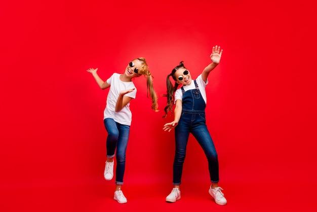 Фото всего тела в стиле фанк смешно сумасшедших двух коричневых подружек со светлыми волосами с хвостами, веселых выходных, праздников, танцев, криков, белых, современных костюмов, изолированных на красном фоне