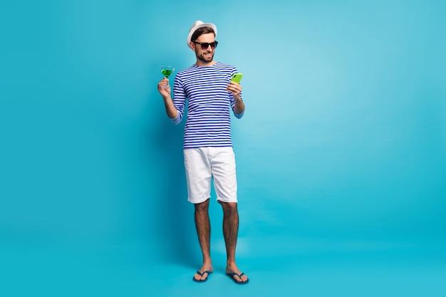 펑키 여행자 남자 검색 전화 음료 녹색 칵테일의 전신 사진 모든 포함 리조트 착용 태양 사양 스트라이프 선원 셔츠 모자 반바지 플립 플롭 절연 파란색