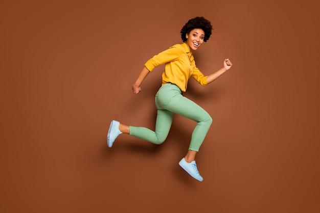 Фотография всего тела смешной темнокожей волнистой дамы, прыгающей вверх в стремительно стремительном торговом центре со скидкой черная пятница в желтой рубашке в зеленых штанах, туфлях изолированного коричневого цвета