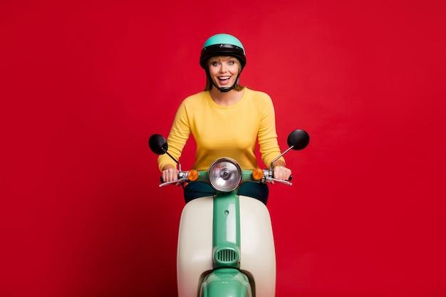 赤い壁に自転車の興奮した顔を運転する面白い女性の全身写真