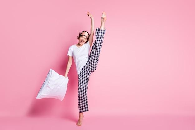 Фотография всего тела смешной дамы держит подушку, поднимает ногу на розовой стене