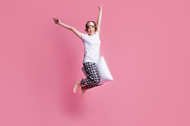 おかしな女性の全身写真は脚の間の高く柔らかい大きな枕をジャンプします