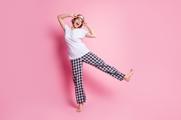 재미 있은 여자의 전신 사진은 분홍색 벽에 파자마를 입고 다리를 올립니다.