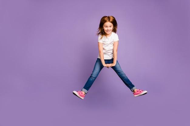空中で喜んで高くジャンプする面白い小さな生姜の女性の全身写真
