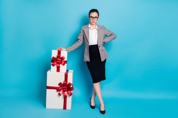 Полное фото тела девушки получить стопку стопки подарочной коробки носить серый черный пиджак стиль блейзер туфли на шпильке изолированный синий цвет фона