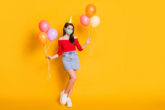 医療マスクホールドバルーンの女の子の全身写真は、お祝いの機会のお祝いをお楽しみください赤いトップデニムジーンズミニショートスカート脚コーン孤立した明るい輝き色の背景